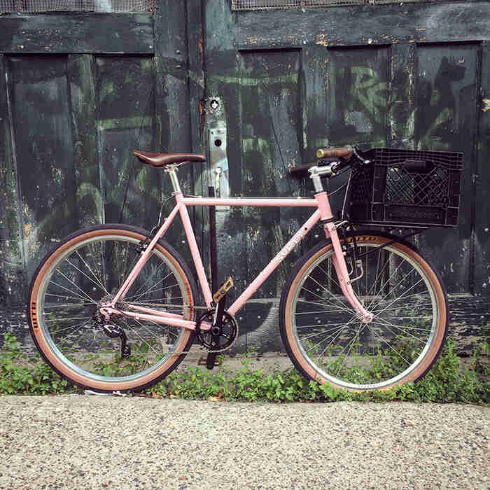 Ride side view of a pink Surly Pack Rat bike with a milk crate on front rack and old wood doors in the background