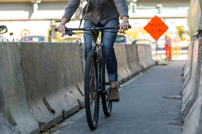 Urban commuter cyclist riding in jeans through road construction path