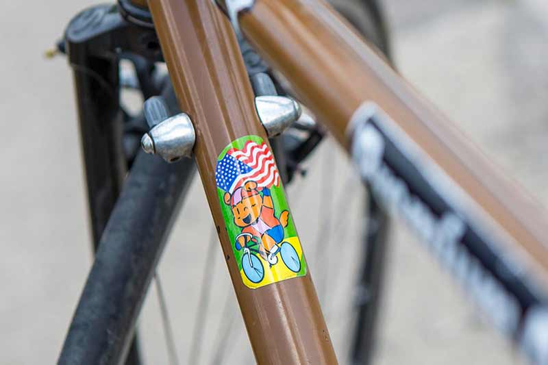 Close-up of brown Surly bike with sticker on downtube of cartoon animal biking one-handed and holding American flag