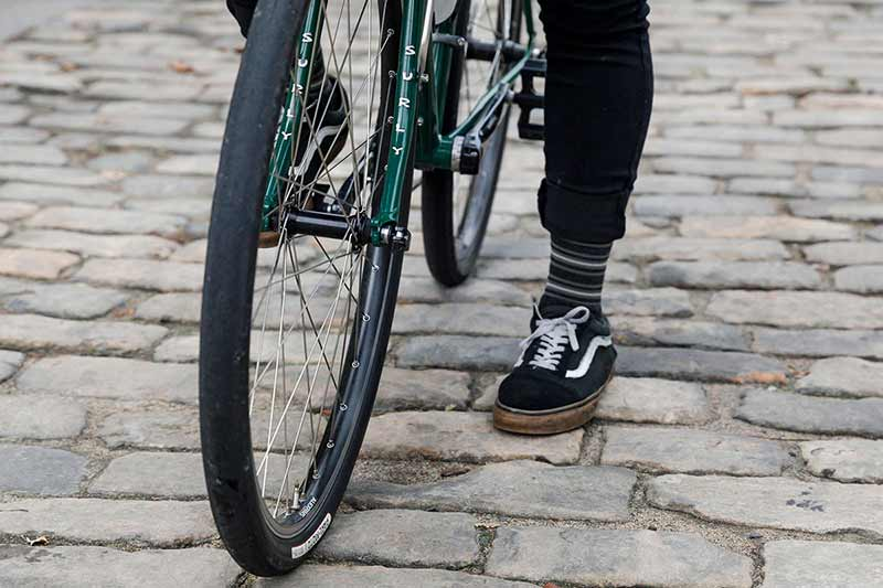 Cyclist standing over bike with one foot down on brick road