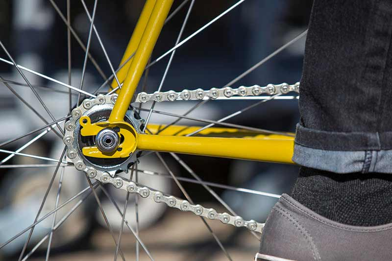 Close-up of drive-side rear wheel on yellow single speed bike