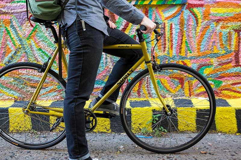 Cyclist in casual clothing standing over yellow Surly bike with one foot on pedal and one foot on ground in front of mural