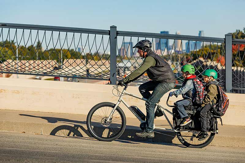 Cyclist riding Surly Big Easy cargo ebike with two children on back over highway bridge with skyscrapers in background