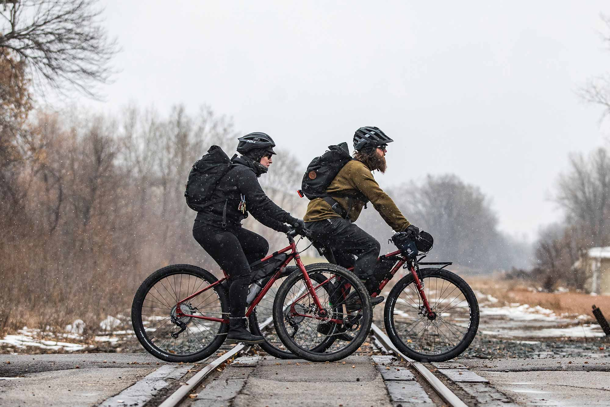 Two bike commuters riding on road in warm clothing, helmets and backpacks in light snow