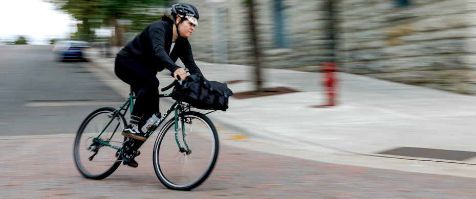 Cyclist riding a black Surly Pack Rat bike, leans into a left turn at the bottom of a hill on a city street