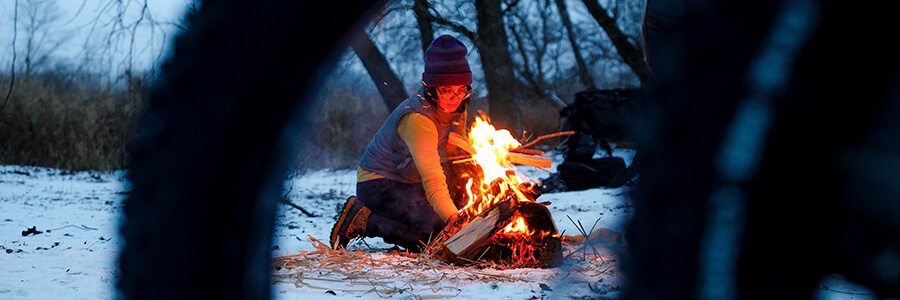 Person lighting a camp fire before sunset
