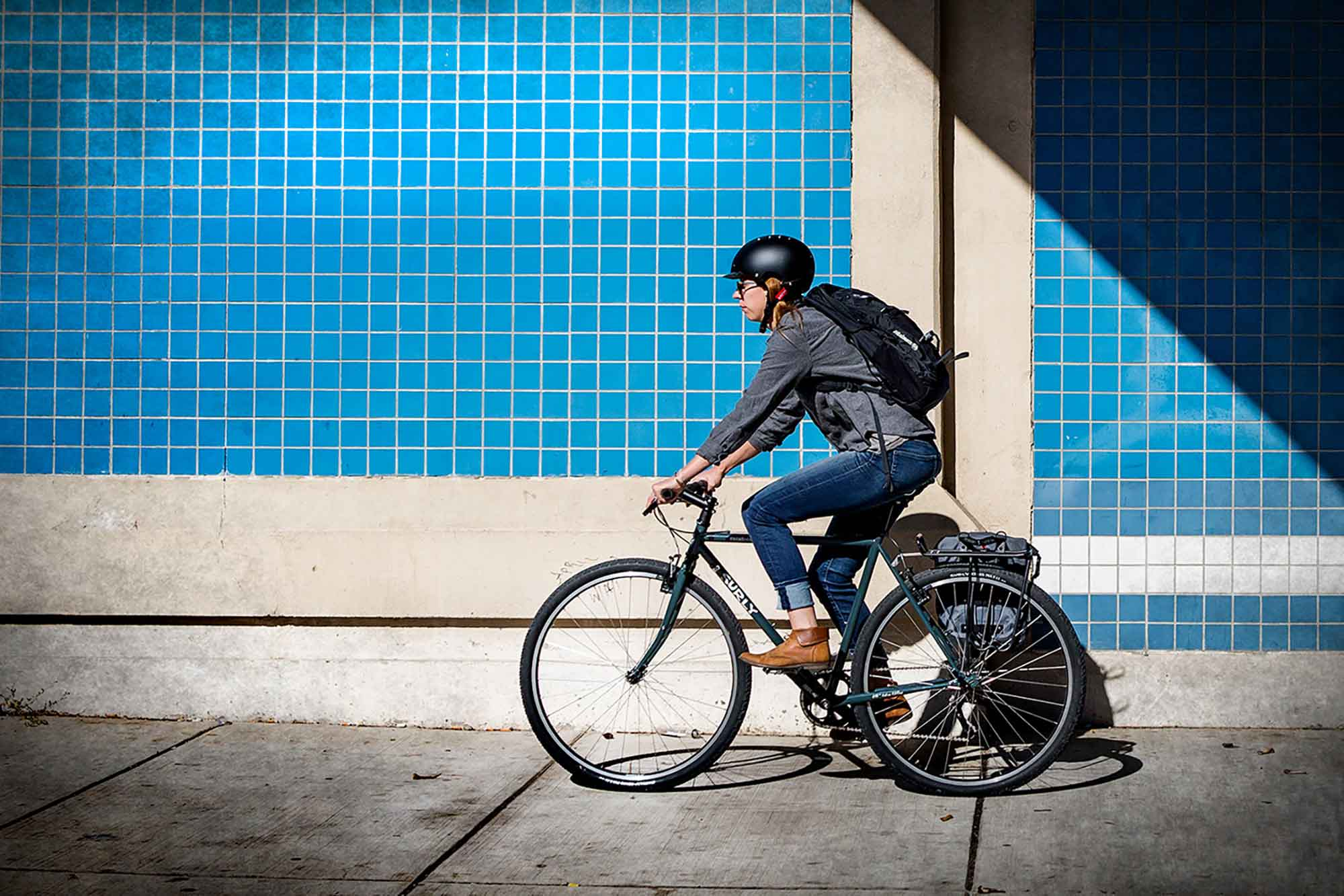 Cyclist rides a Surly bike on a sidewalk alongside a building with blue tiles on it