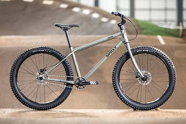 Gray Surly Lowside side view with 26-inch wheels, on indoor BMX track