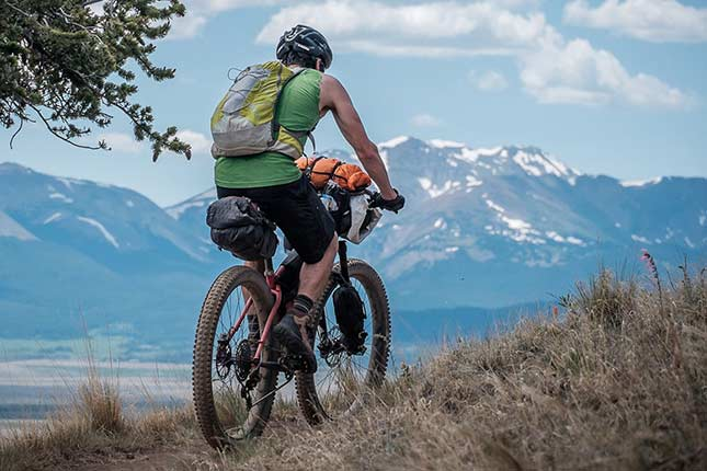 Mountain biker with helmet, backpack and bikepacking gear attached to bike on trail with mountains in background