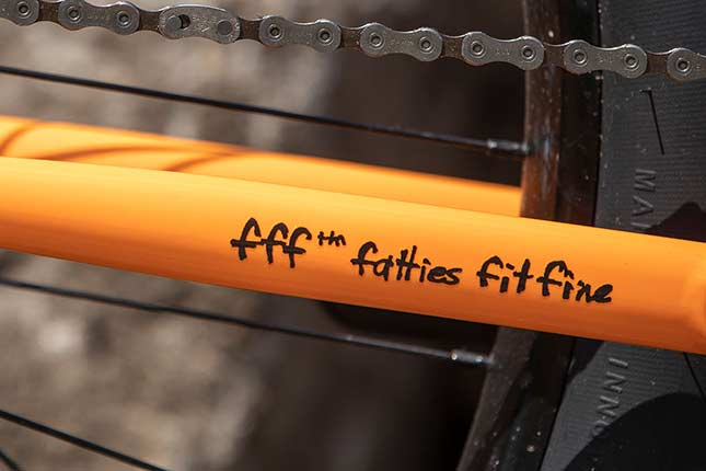 fff ™ fatties fit fine decal on chain stay of orange Surly bike showing part of chain and rear wheel