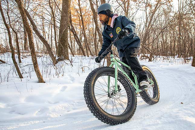Mountain biker wearing helmet and warm clothing riding mint colored Surly Fat Bike on snow covered off-road trail