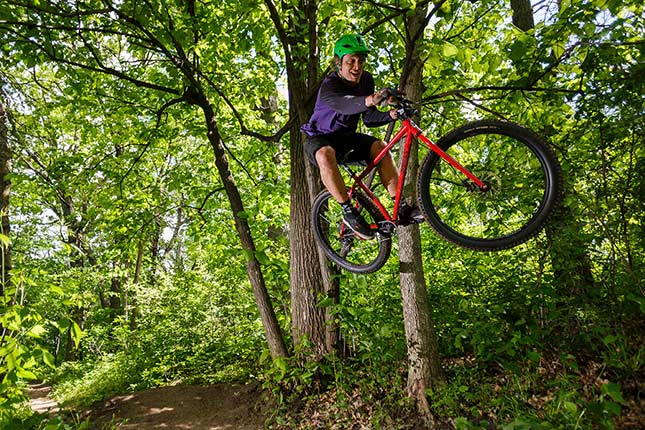 Mountain biker with green helmet jumping red Surly Krampus on off-road trail in the woods