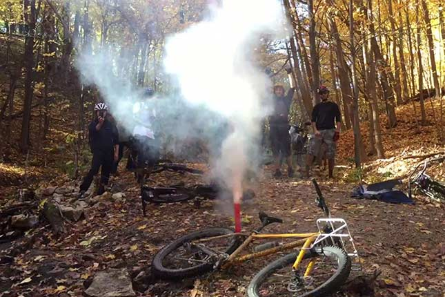 Group of bikers in woods standing around with bikes laying on ground with smoke erupting from red firework tube