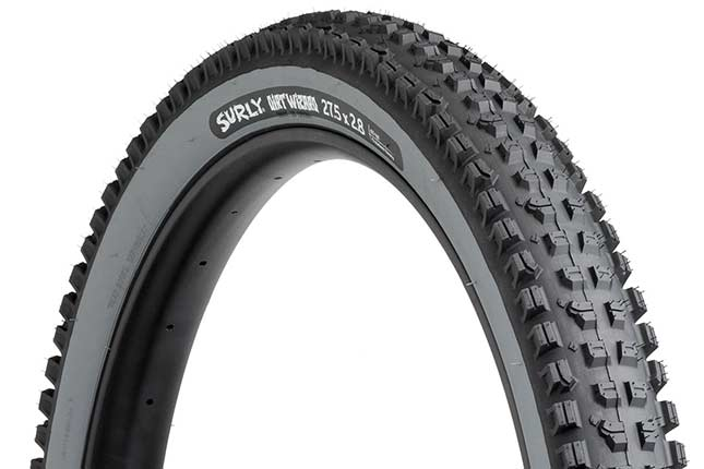 Surly Dirt Wizard 27.5 x 2.8 inch tire with slate gray sidewall showing tread with hot patch on white background