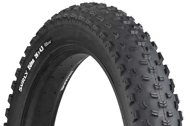 Surly Edna 26 x 4.3 inch fat bike tire mounted on rim showing tread and sidewall with white hot patch on white background