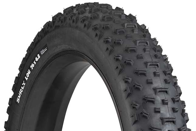 Surly Lou 26 x 4.8 inch fat bike tire mounted on rim showing tread and sidewall with white hot patch on white background