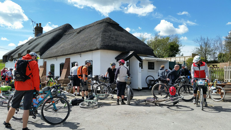 A group of cyclists, with bikes scattered around, and a building with a grass roof in the background
