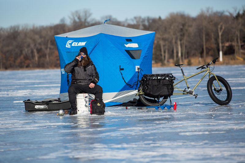Person on a bucket on a frozen lake next to a Surly Big Fat Dummy bike, with a ice fishing shelter in the background