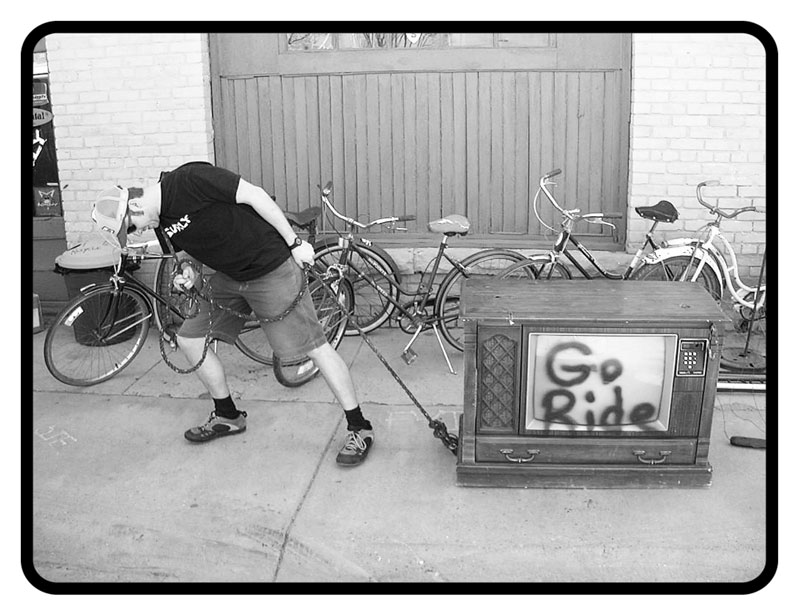 Person pulling a tube TV across a sidewalk, with bike lined up in front of a building in the background