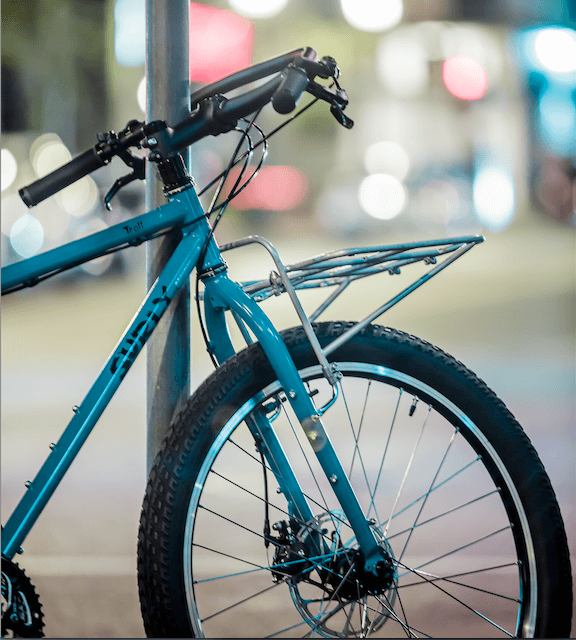 Surly Troll bike - turquoise - with 24-Pack Rack - parked against a steel pole - cropped, right side, front end view