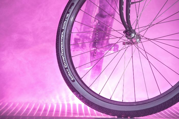 Profile of a Surly Extra Terrestrial bike tire with gray slate sideways mounted on rim with spokes and lavender spoke and lights in the background