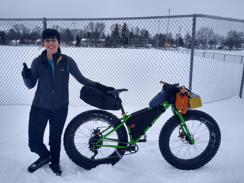 A cyclist poses at the back of a Surly fat bike, green, on a cloudy day in a snowy field with a chain link fence behind