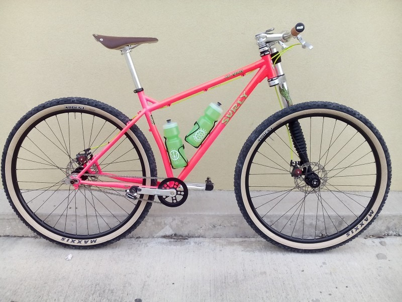 Right side view of a pink Surly Karate Monkey bike, parked next to a cement curb with a tan wall behind