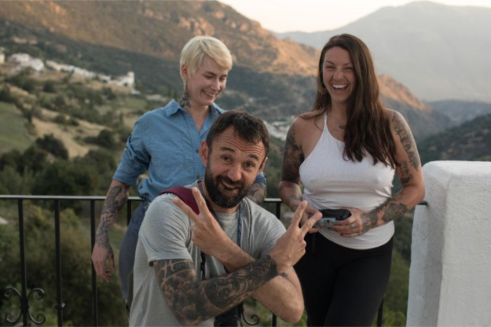 Three friends posing on a patio in the mountains with one kneeling giving peace signs with hands