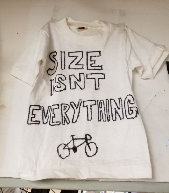 White T-Shirt with the words 'size isn't everything' and a picture of a bike is taped to a white wall