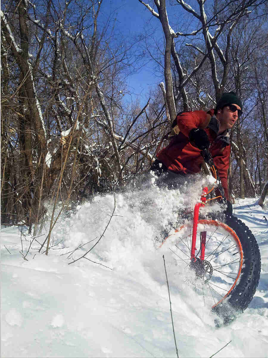A cyclist, riding a red Surly Pugsley fat bike, thrashes through deep snow in the woods