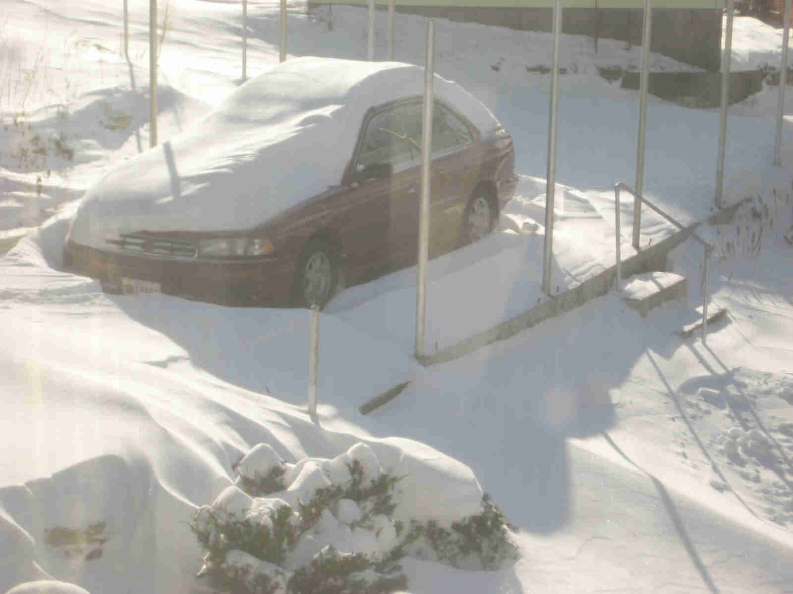 Downward view of a red car buried in deep snow