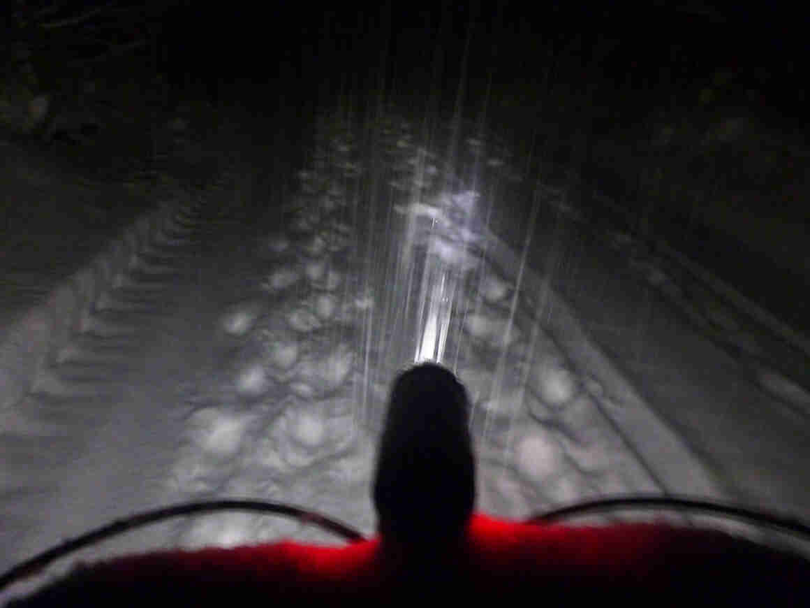 The front of the handlebar, with a headlight, on a bike that's facing down a snow covered trail at night