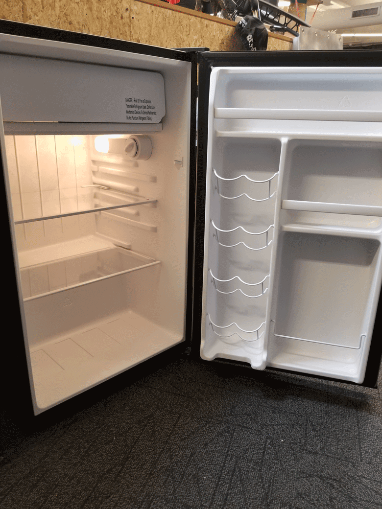 Angled view from the left side of a empty black refrigerator with fully open in front of an OSB wall