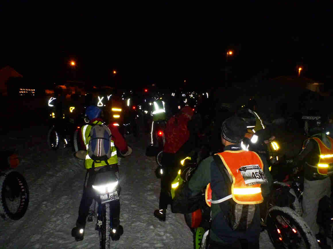 Rear view of a group of winter cyclists, standing over their bikes on snow, at nighttime