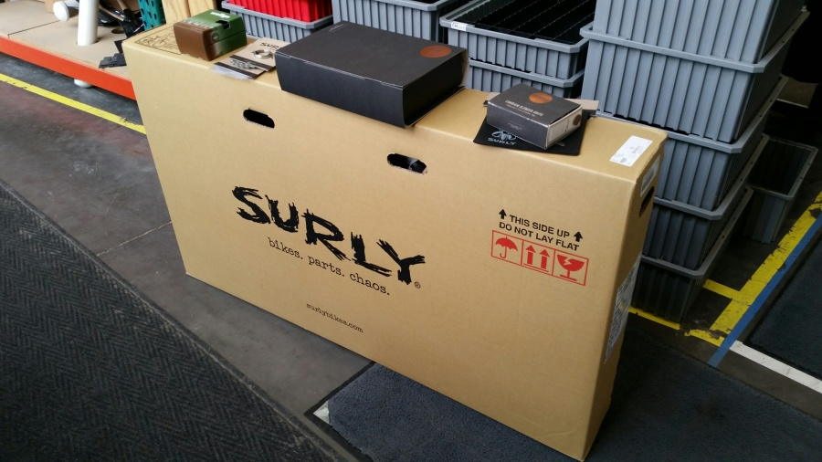 A Surly bike box on a sidewalk, with plastic totes in the background