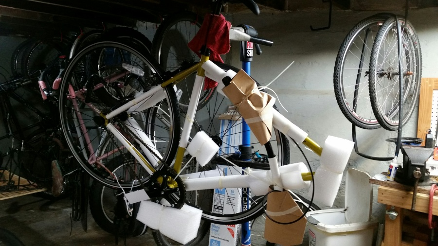 Right side view of a partially assembled bike on a stand, in a room with bikes and parts in the background