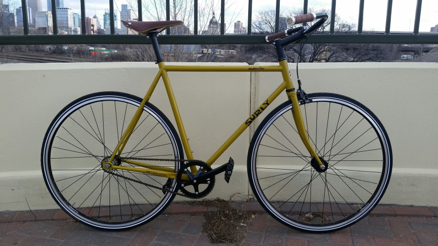 Right profile of a Surly Steamroller bike, yellow, in front of a wall on a bridge, with a city skyline in the background