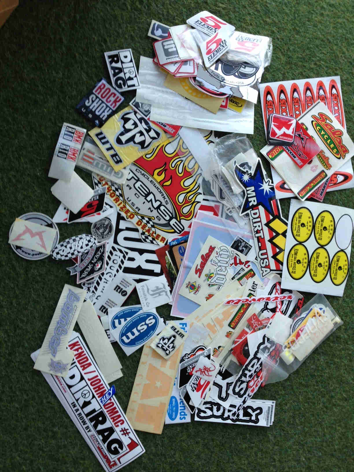 A collection of stickers, scattered on laying flat on each other, on top of a green surface