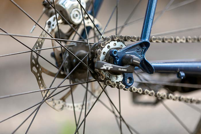 Drive-side rear hub, single speed cog, chain, quick-release, dropout detail, rear disc brake caliper and rotor
