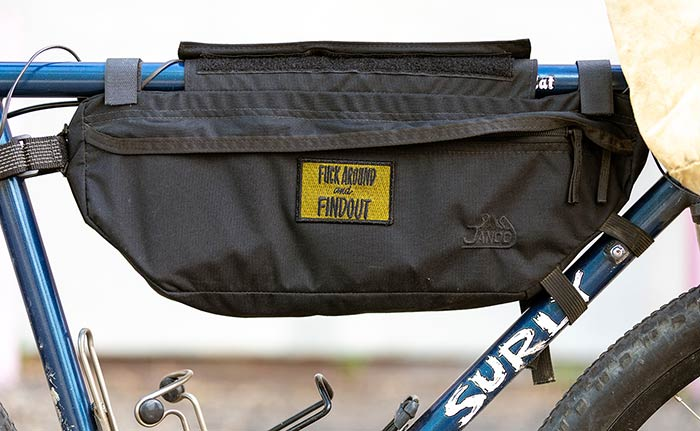 Side-view showing frame bag with yellow patch applied, blue frame and white Surly decal and two water bottle cages