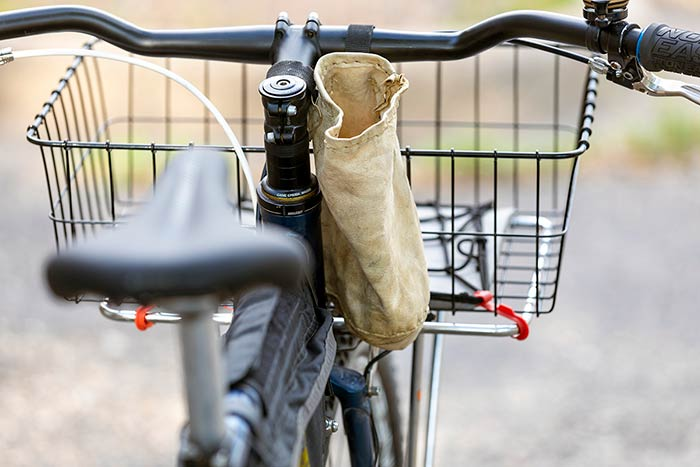 Rear view of bike showing homemade leather handlebar feed bag, rack/basket, handlebar with bell, brake levers and lock-on grips with blue collars and saddle