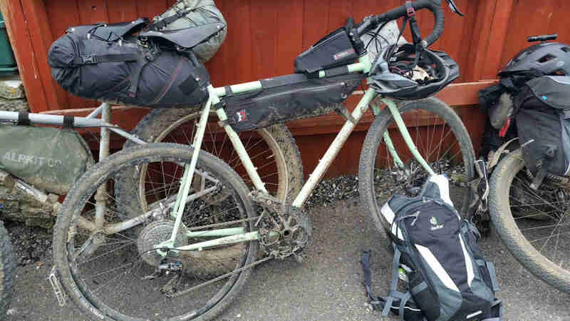 Right profile of a muddy Surly bike, loaded with gear leaning on a red wood fence