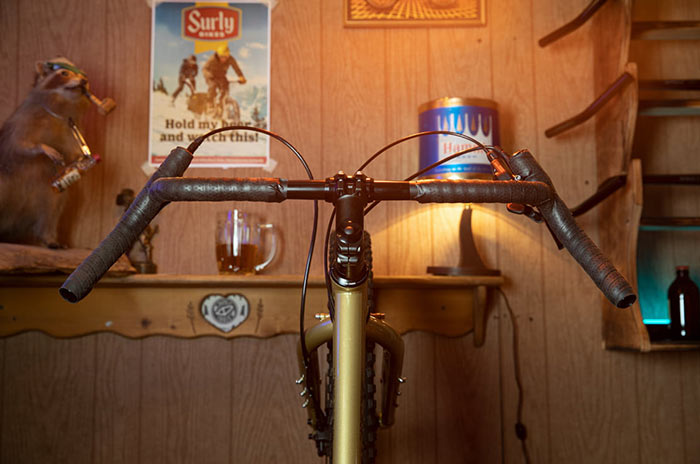 Surly Corner Bar with black bar tape up on gold Surly Karate Monkey against wood paneled wall with beer mug in background