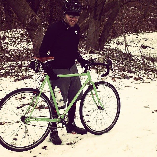 Right side view of a green Surly bike parked on the snow, with a cyclist standing behind and woods in the background