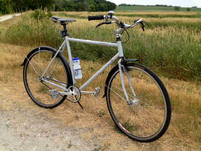 Right side view of a white Surly Cross Check bike, parked next to a gravel road, with a grassy field in the background