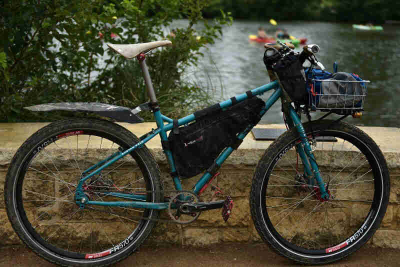 Right profile view of a turquoise, Surly Troll bike, against a stone wall, with trees and a pond in the background