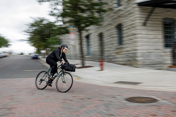 Front, angled, right side view of a cyclist on a green Surly Pack Rat bike, making a swift left turn on a city street