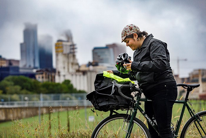 Left side view of a cyclist stand over a green Surly Pack Rat bike in tall grass and a city skyline in the background