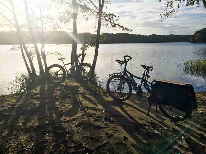 Left side view of a Surly Big Dummy bike, parked on dirt bank of a lake, next to another bike