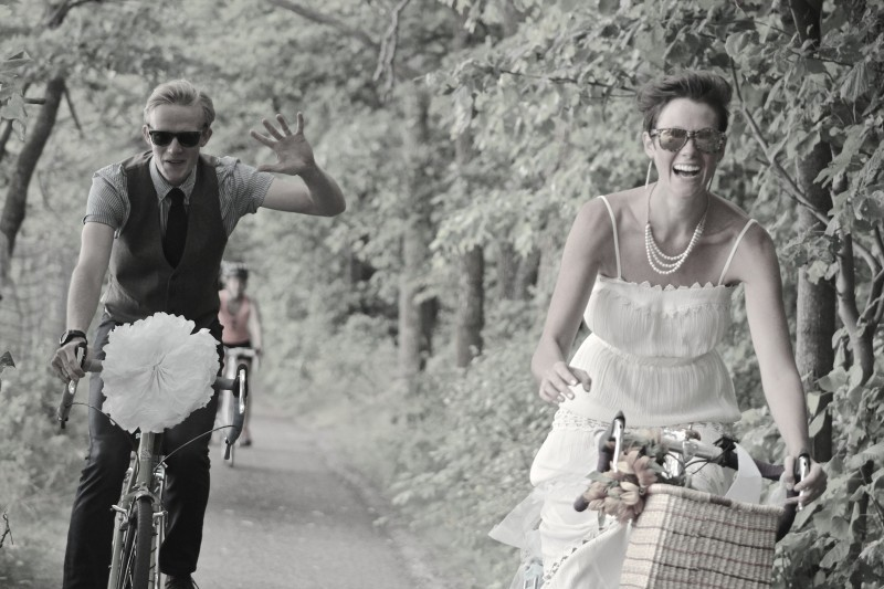 Front view of two people wearing wedding attire, riding bike down a paved trail with trees on the sides